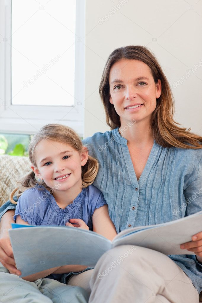 Portrait of a mother reading a book to her daughter in a living room — Stock Photo #11210694