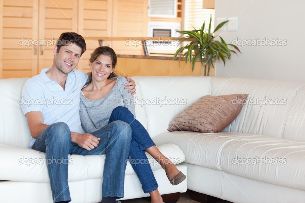 Couple sitting on a sofa while looking at the camera — Stock Photo #11211248