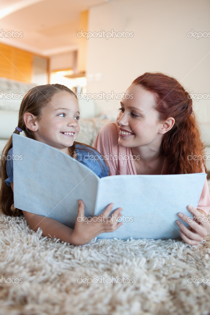 Mother and daughter on the floor looking at magazine together — Stock Photo #11212164