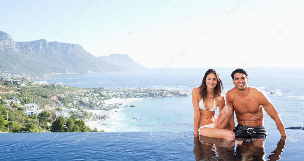 Couple sitting on the pool edge with landscape in the background — Stock Photo #11212746