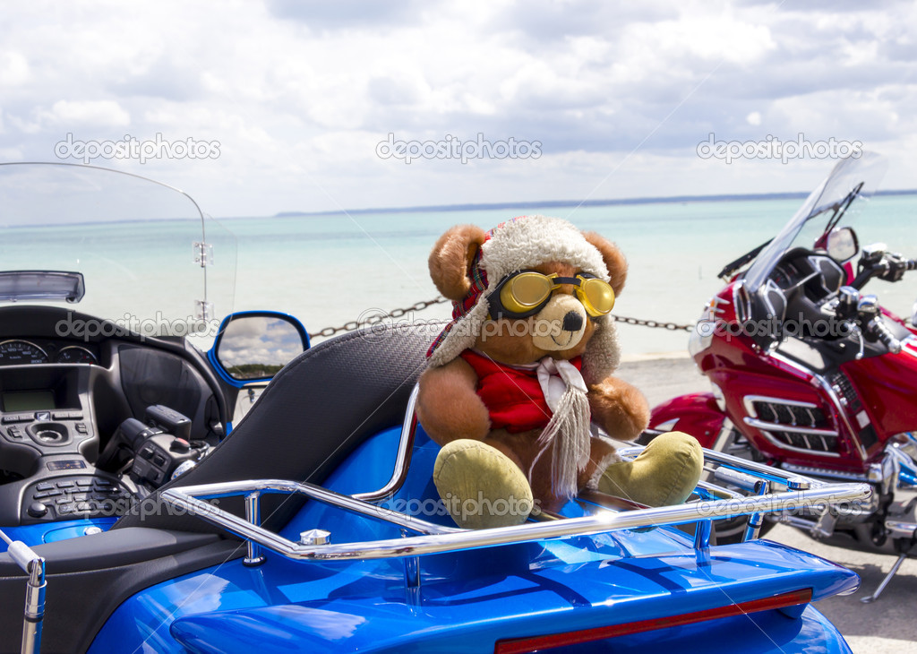 Teddy Bear toy on the blue motorbike on a seashore — Stock Photo #10787867