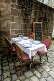 Dining table in front of the french medieval buildings — Stock Photo