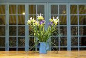 Piękne wiosenne kwiaty w niebieski czajniczek emaliowana na drewno — Zdjęcie stockowe