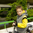 Young cute school boy with bicycle on the bridge — Stockfoto