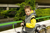 Young cute school boy with bicycle on the bridge — Stock Photo