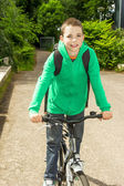 Young school boy with backpack on a bicycle — Stock Photo