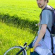 Man cyclist relaxing against the background of green fields in s — Stock Photo