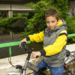 Stock Photo: Young cute smiling school boy with bicycle on the bridge