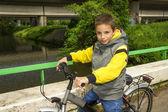 Genç sevimli gülümseyen okul çocuk bisiklet köprü ile — Stok fotoğraf