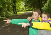 Portrait of two surprised boys, tweens are pointing and hugging — Stock Photo
