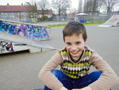 Cute Smiling Boy Sitting In Playground — Stock Photo