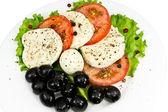 Salade met een plaat van mozzarella, tomaten, olijven en kruiden — Stockfoto