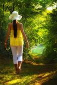 Mladá žena chůze po silnici v lese — Stock fotografie