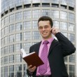 Attractive young businessman using a cell phone in front of a modern office building — Stock Photo