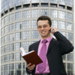 Attractive young businessman using a cell phone in front of a modern office building - Stock Photo