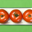 A photo of three tomatoes on the plate - Stock Photo