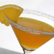A photo of martini glass with orange cocktail and a piece of citrus — Stock Photo