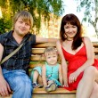 Young family relaxing in the park — Stockfoto