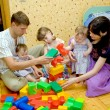 Big family building a house from toy cubes — Stock Photo