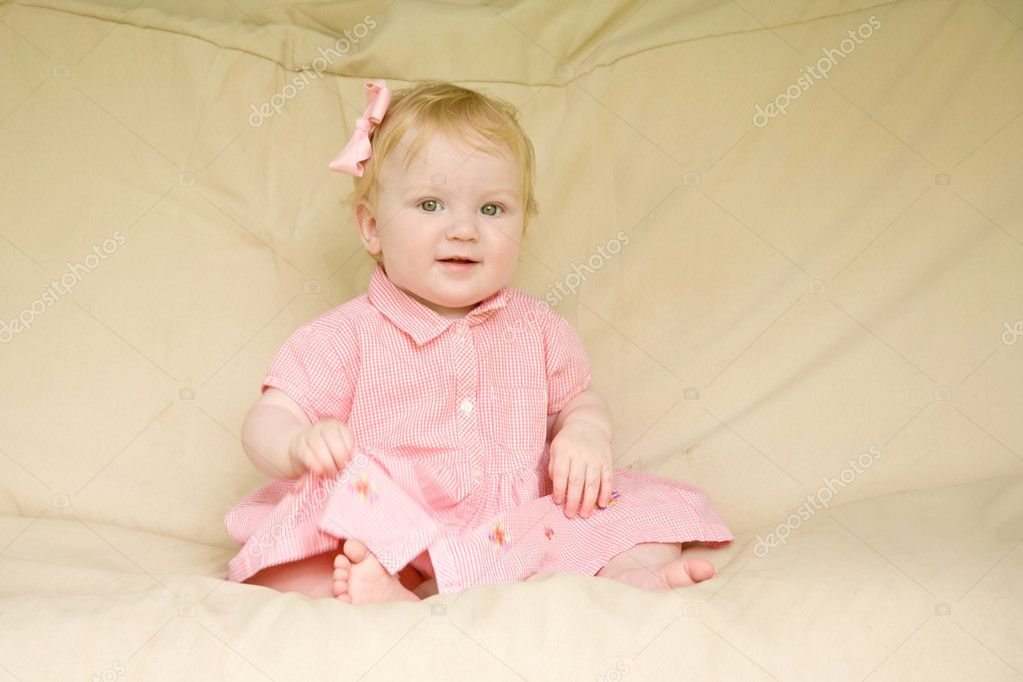 Beautiful little baby girl with blond hair and blue eyes and smiling while sitting on a beige background. The girl wearing a checkered pink dress and pink bow. — Stock Photo #11026107