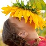 Baby riechen eine große Sonnenblume — Stockfoto