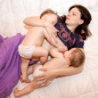 Breast feeding two little sisters twin baby girls - Stock Photo
