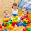 Preschooler and two twins baby building of blocks — Stock Photo