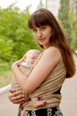 Newborn baby sleeping in sling, in embrace of mother. — Stock Photo