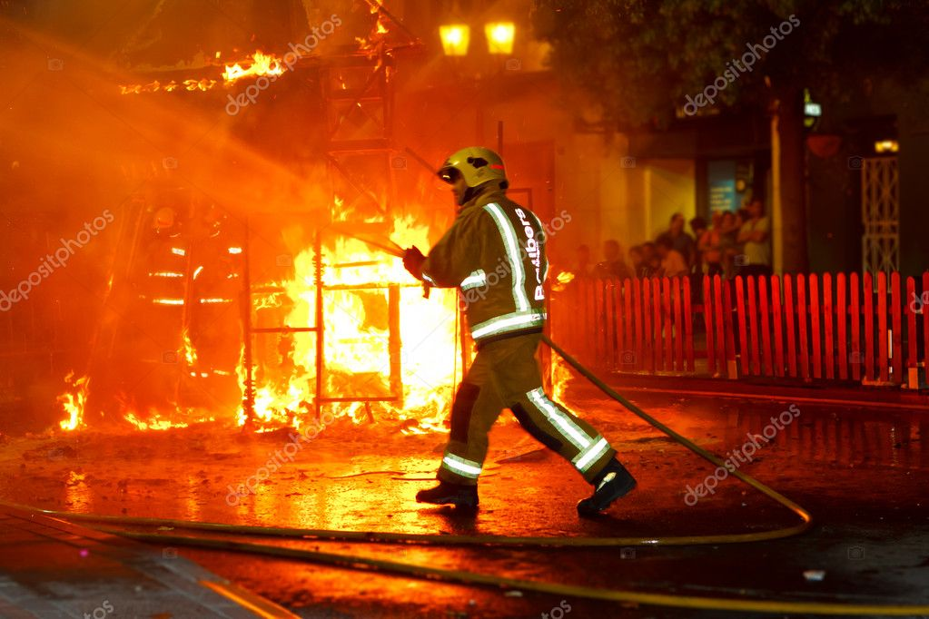 Firefighter putting out fire with water hose pressure — Stock Photo #11898739
