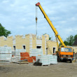 Construction of the new house with a crane. - Stock Photo