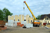 Construction of the new house with a crane. — Stock Photo