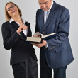 Beautiful business woman with male colleague reading a book — Stock Photo