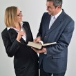 Business colleagues working together and reading a book — Stockfoto