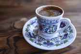 Traditional Turkish coffee served in cup on wooden table — Stock Photo