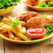 Fried drumsticks with french fries - Stock Photo