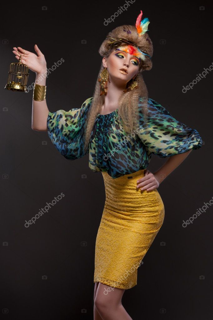 Model with a creative makeup and hair styling posing with a small birdcage — Stock Photo #11531892