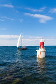 The lighthouse and the sail — Stock Photo
