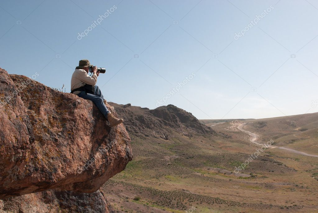 Photographer takes pictures sitting on the big hanging stone — Stock Photo #12161735