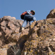 Stock Photo: Tourist rises on rock