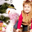 Foto Stock: Girl under Christmas tree with gifts
