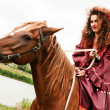 Beautiful gypsy girl in a red dress. He sits on the horse — Stock Photo