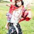 Foto Stock: Beautiful gypsy girl in red dress with baby. Guesses on cards