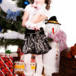 A girl stands near a Christmas tree — Foto Stock