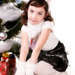A girl sitting near a Christmas tree — Foto Stock