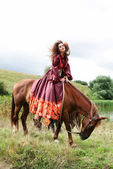 Beautiful gypsy girl in a red dress. He sits on the horse — Стоковое фото