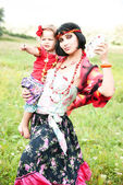 Beautiful gypsy girl in a red dress with the baby. Guesses on the cards — Stock Photo