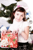 A girl under the Christmas tree with gifts — Stock Photo