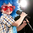 Stock Photo: Boy sings into microphone
