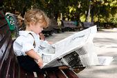 阅读一份报纸的女孩 — 图库照片