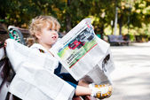Girl reading a newspaper. — Stock Photo